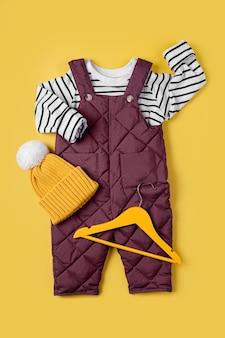 Calça quente e blusa listrada com chapéu em fundo amarelo. conjunto de roupas de bebê para o inverno. roupa de moda infantil.