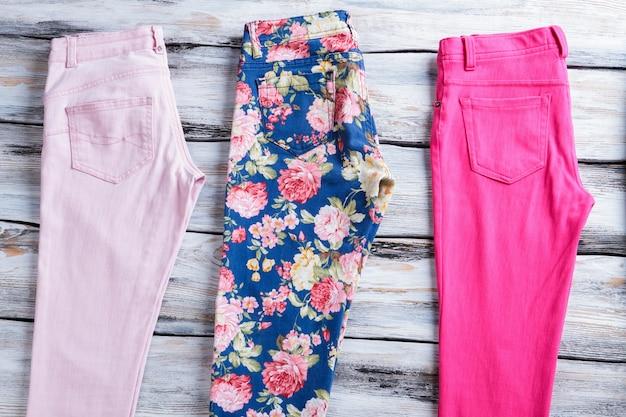Calça rosa claro e floral. calças de menina em fundo de madeira. roupas coloridas de verão. algodão de qualidade e estampado com estilo.