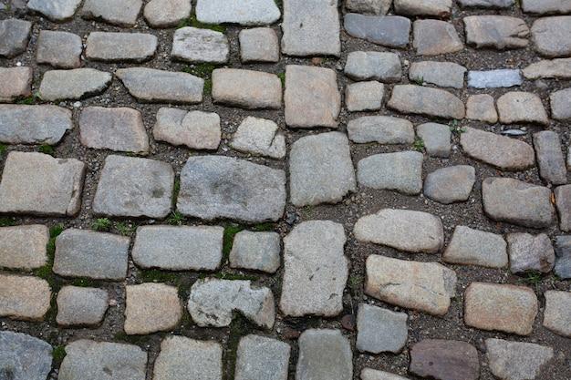 Calçada de paralelepípedos molhada após a chuva no centro histórico da cidade velha. foto de close