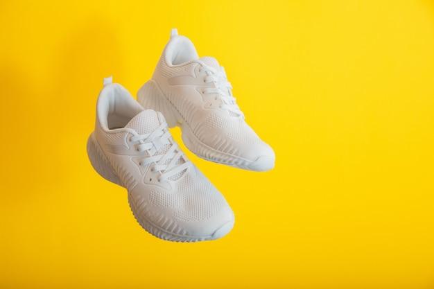 Calçado de sapatos esporte branco levitação na parede amarela. sapatos de tênis brancos voam sobre fundo de cor amarela com espaço de cópia. par de tênis esportivos masculinos.
