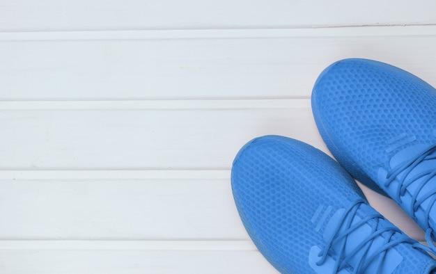 Calçado desportivo azul para correr no chão de madeira branco. vista do topo.