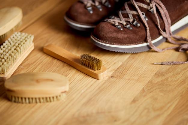 Calçado plano, vista de cima, com acessórios de botas de camurça, escova na mesa de madeira. manutenção de calçados capturada, espaço de cópia, para texto.