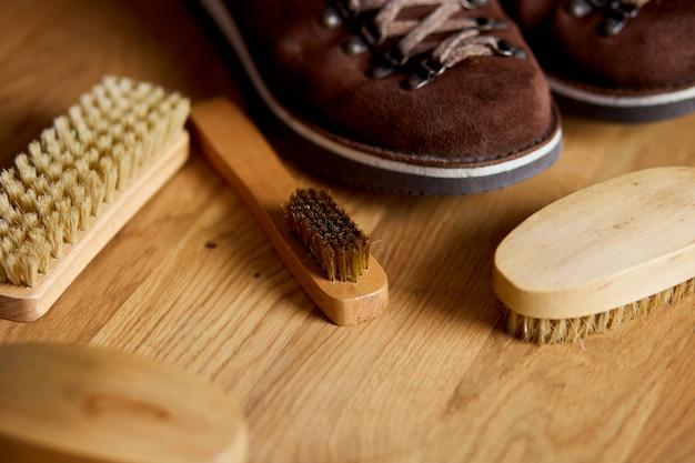 Calçado plano, vista de cima, com acessórios de botas de camurça, escova na mesa de madeira.