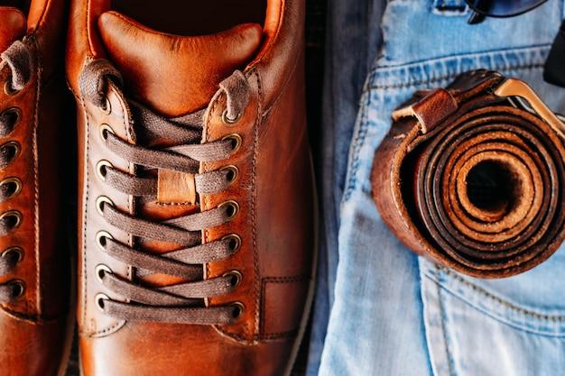 Calçados casuais de couro de brown, calças de brim e fim da opinião superior da correia acima. conceito de moda