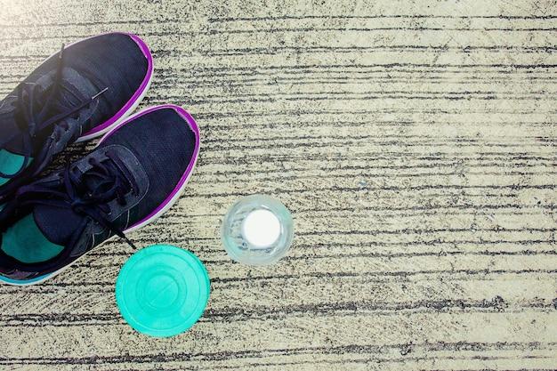 Calçados esportivos com garrafa e haltere de cor verde no chão ou rua