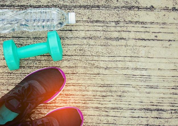 Calçados esportivos com garrafa e haltere de cor verde no chão