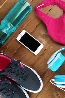 Calçados esportivos e roupas na mesa de madeira