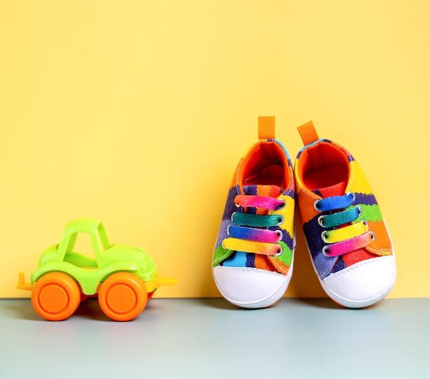 Calçados esportivos jeans multicoloridos para o bebê em um fundo amarelo com um carro infantil b ...
