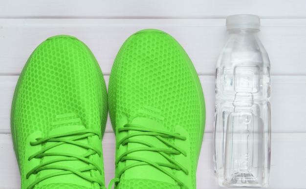 Calçados esportivos verdes para correr, garrafa de água no piso de madeira branco. vista do topo.