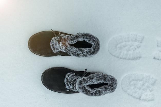 Calçados femininos quentes com rastros na neve. sapatos de inverno femininos bonitos e práticos.