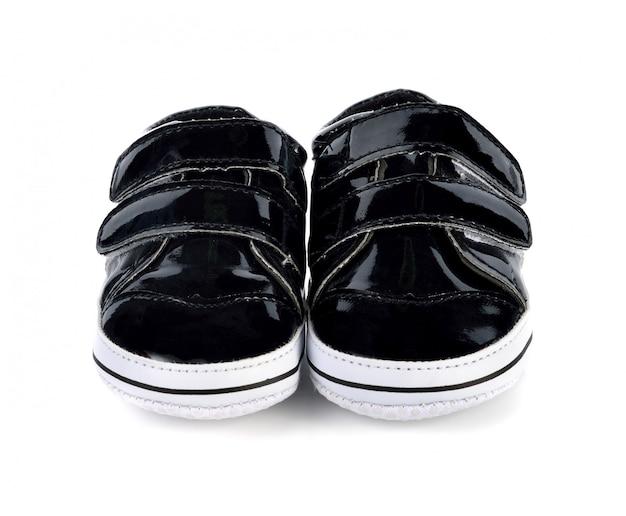 Calçados infantis isolados sobre o branco