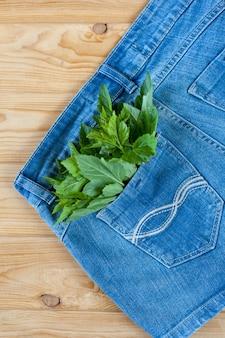 Calção jeans azul com folhas verdes no bolso sobre fundo de madeira. foto de alta qualidade.