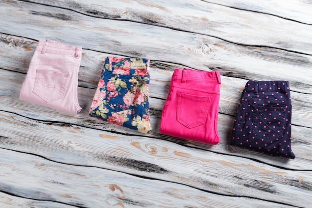 Calças casuais brilhantes de mulher. calças de cores diferentes. calça dobrada em vitrine branca. produtos importados de alta qualidade.