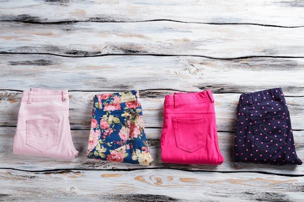 Calças coloridas diferentes. calças casuais em fundo de madeira. somente produtos genuínos. venda de vestuário de qualidade.