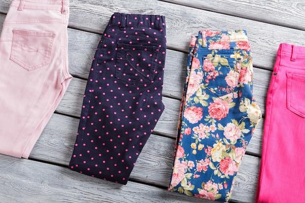 Calças da marinha com pontos-de-rosa ladys azul e rosa calças vestimentas deitado na mesa cinza venda de primavera com ...