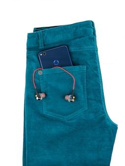 Calças de brim bonitas verdes com os auscultadores no bolso isolado no branco.