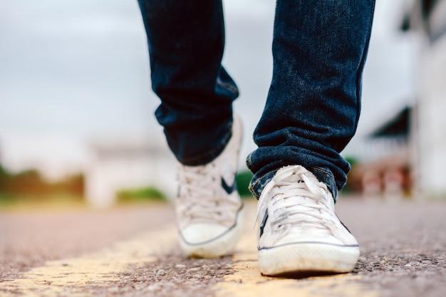 Calças de brim dos homens e sapatas da sapatilha na estrada.