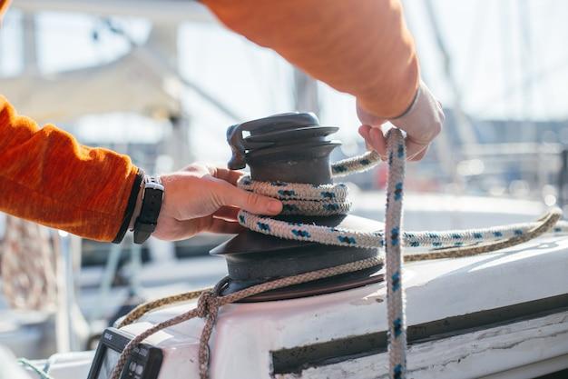Calças de marinheiro ou iatista profissionais e cabos de tensão ou cabo de aço em guincho mecânico em veleiro ou iate