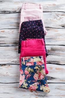 Calças de menina com padrão diferente. calças elegantes de cores vivas. mercadoria com desconto na vitrine. desconto sazonal em boutique.