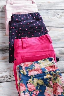 Calças de senhora com estampado cheio de estilo. pontos rosa em calças marinho. novas roupas da moda em exposição. preços mais baixos para itens autênticos.