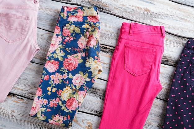 Calças dobradas em cores diferentes. calças da moda em fundo de madeira. seleção de mercadoria na prateleira. compre um e ganhe dois.