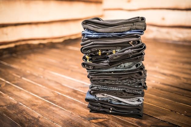 Calças femininas negras empilhadas no chão de madeira