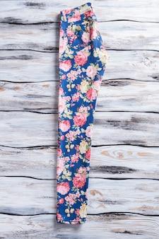 Calças florais claras, calças elegantes com fundo de madeira, roupas femininas com estampa colorida q ...