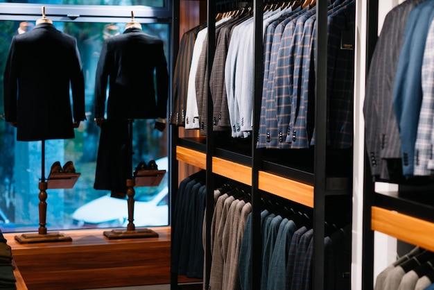 Calças nas mãos dos homens em uma loja de roupas, close-up.