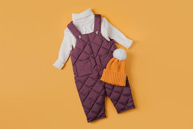 Calças quentes e suéter branco com chapéu em fundo laranja. conjunto de roupas de bebê para o inverno. roupa de moda infantil.