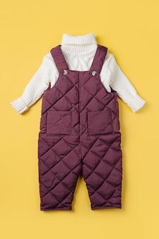 Calças quentes e suéter branco sobre fundo amarelo. conjunto de roupas de bebê para o inverno. roupa de moda infantil.