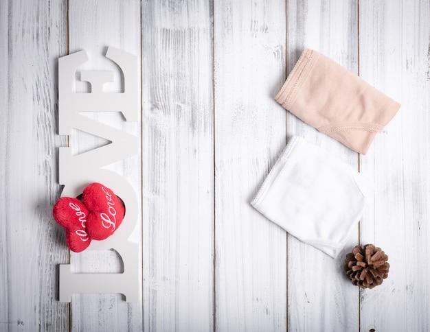 Calcinha de mulher dobrada, placa de amor, corações e pinha