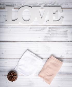 Calcinha de mulher dobrada, placa de amor e pinha