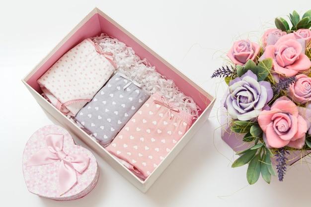 Calcinha dobrada de algodão de várias cores numa caixinha com flores artificiais em fundo branco. conjunto de roupa interior de mulher. vista do topo.