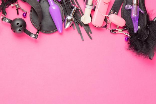 Calcinha feminina, plug anal, vibrador, vibrador, mordaça, grampos de mamilo e outros no fundo rosa.