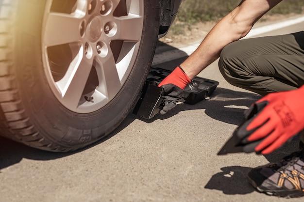 Calços de roda sob o pneu do carro nas mãos do motorista do homem da estrada