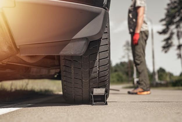 Calços de roda sob o pneu do carro no homem da estrada em pé próximo à vista inferior