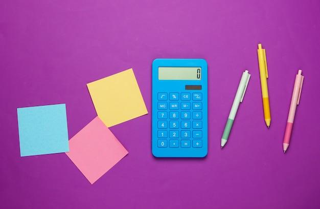Calculadora azul com canetas e folhas coloridas de papel em roxo.