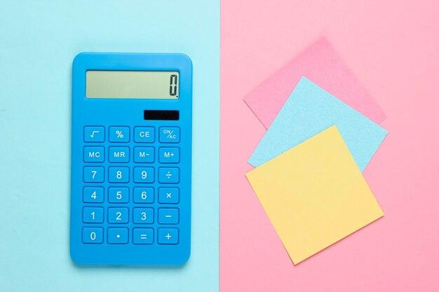 Calculadora azul com folhas de papel coloridas em azul rosa. ferramentas de escritório