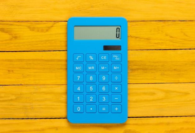 Calculadora azul em uma madeira amarela