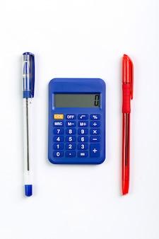 Calculadora azul uso de mão de contabilidade para assuntos de negócios, juntamente com duas canetas uma vista superior em branco