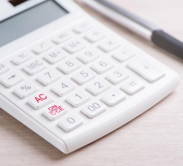 Calculadora branca e caneta na análise de mesa de madeira brilhante e estatísticas do conceito de risco de investimento de lucro financeiro cópia espaço macro close-up