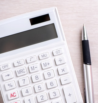 Calculadora branca e caneta na análise de mesa de madeira brilhante e estatísticas do conceito de risco de investimento de lucro financeiro cópia espaço vista superior plana lay