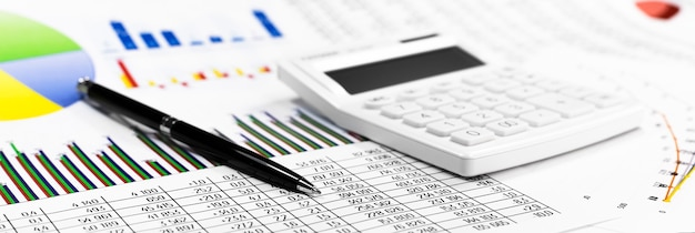 Calculadora branca, moedas e caneta preta