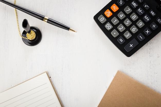 Calculadora, caneta, caderno de papel em uma mesa de madeira