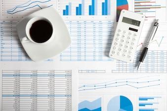Calculadora, caneta e gráficos financeiros