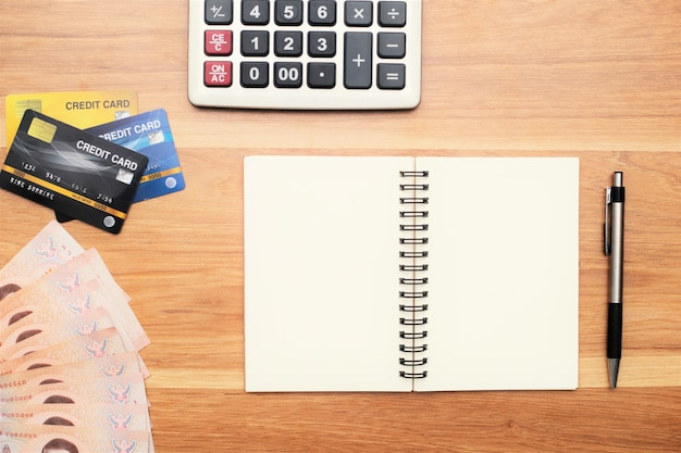 Calculadora cartões de crédito e dinheiro, notas tailandesas, canetas na mesa
