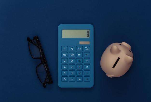 Calculadora, cofrinho e óculos no fundo azul clássico. cor 2020. vista superior.