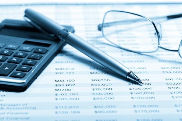Calculadora colocando documentos com óculos e caneta
