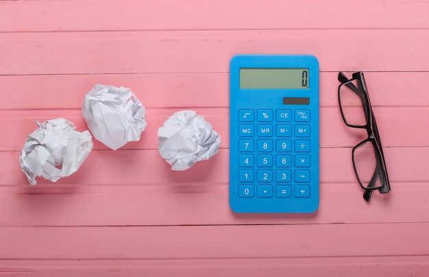 Calculadora com bolas de papel amassadas, óculos em uma madeira rosa.
