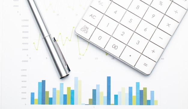 Calculadora com caneta sobre dados financeiros. conceito de pesquisa de negócios e finanças.